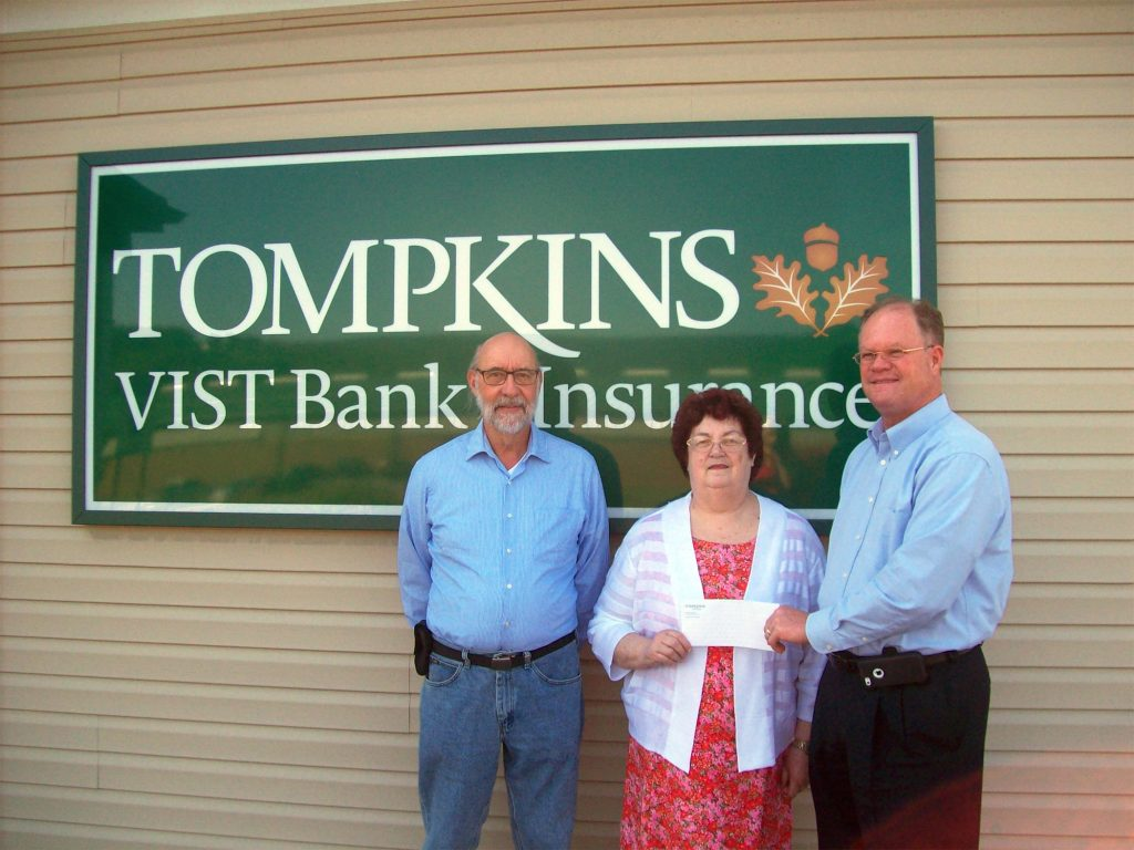 Tompkins Vist Bank presents funds to the Schuylkill County Fair which will provide assistance in keeping the gate admission at a very affordable level for all who attend the Fair August 1 through the 6. Pictured are from left, Charlie Kershner, entertainment booking agent for SCF, Grace Karrer, SCF Entertainment Chairman and Joe Hammond,  Vice President for Tompkins Vist Bank.